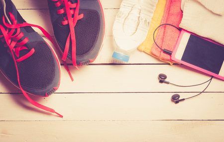 gym shoes: Set for sports activities on white wooden background,vintage color toned image Stock Photo
