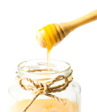 drizzler: Jar of honey with wooden drizzler isolated on white background Stock Photo