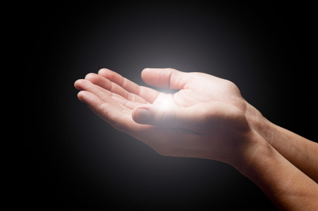 worship praise: hands open with glowing lights Stock Photo