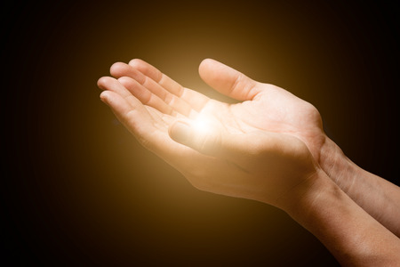praise: hands open with glowing lights Stock Photo