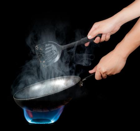 シェフのキッチン上のフライパンの炎と料理