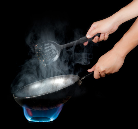 Chef cooking with flame in a frying pan on a kitchen