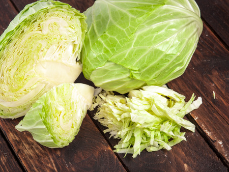 cabbages and cut cabbage on old wooden desk Standard-Bild