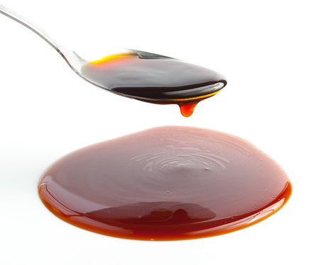 Pouring Soy Sauce on spoon isolated on white 版權商用圖片