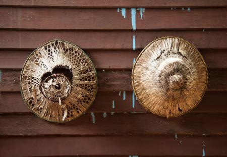 chapeau paille: De vieux chapeaux coniques asiatiques sur un mur en bois Banque d'images