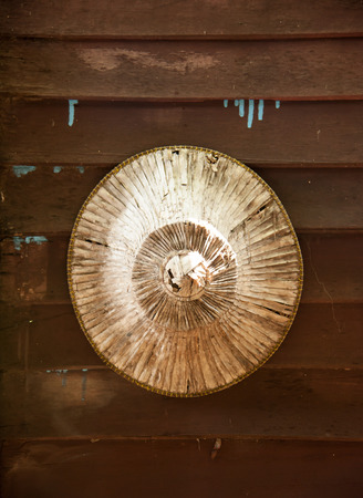 conical hat: Old Asian conical hat on a wooden wall