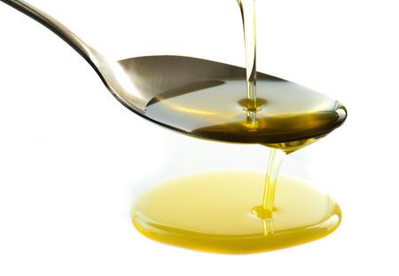 Gieten olie op lepel geïsoleerd op wit