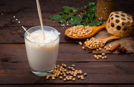 Soy milk splash with beans on wood