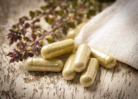 Herb capsules on wood Banque d'images