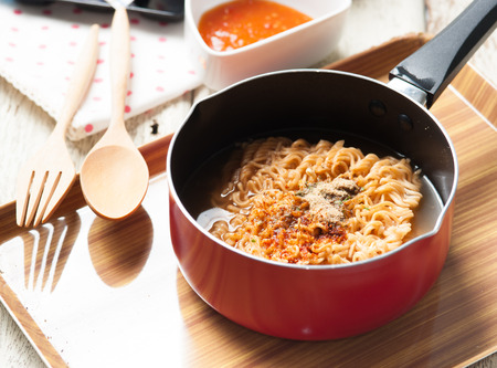 cooked instant noodle: Instant noodles in frying pan on wood