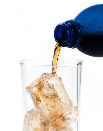 carbonation: Pouring of cola in the glass with ice,Selective focus on glass Stock Photo