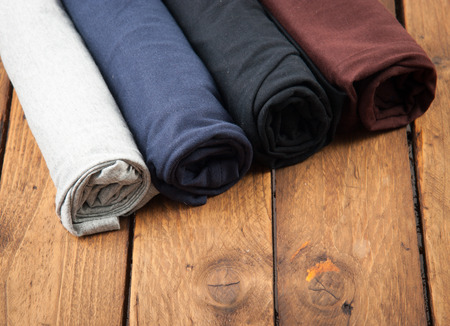 Rolled T Shirts on wood background
