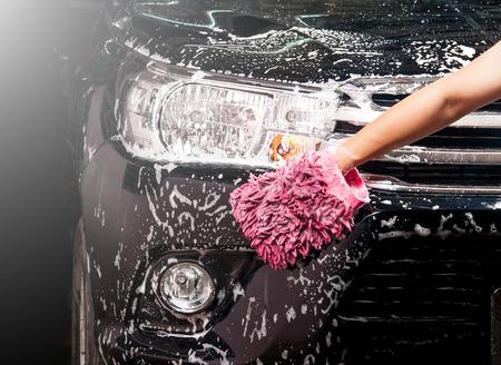 布で石鹸黒の車を洗う人