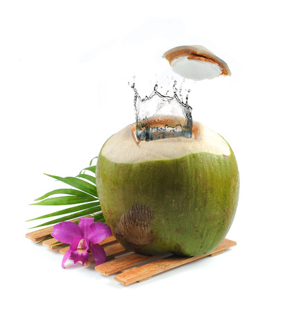 noix de coco: Noix de coco fra�che avec les projections d'eau sur fond blanc Banque d'images