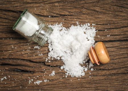 salt shaker: salt sprinkled on wooden table