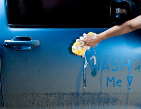 soapy: man washing a soapy blue car with a sponge.
