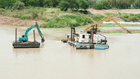 earth moving equipment: excavator machine group works at river