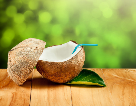 coctel de frutas: Coco y beber pajas sobre madera, los árboles de sol de fondo