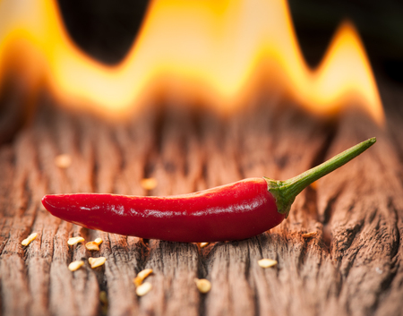 chili: Red chili pepper with fire on wood