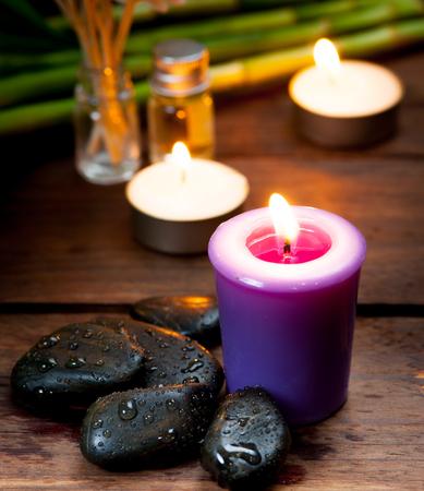 candela: pietre di basalto zen, candele alla lavanda su legno, sfondo scuro ,, Selettiva concentrarsi sulla candela