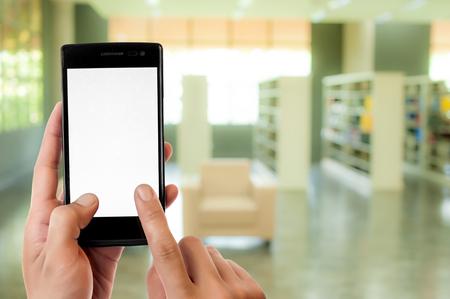 bookshelf digital: Hand holding smart phone on blur library room background