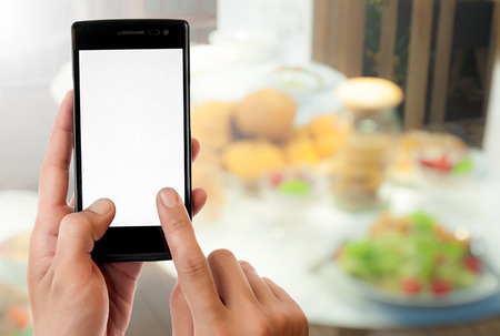 mobile telephone: Hand holding smart phone on blurred food background,nuggets and vegetables