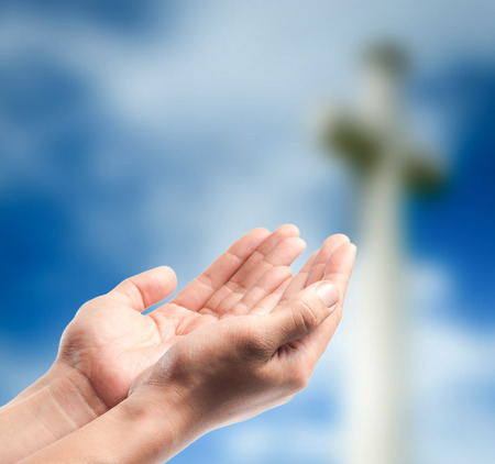 jesus praying: hands praying over blurred the cross on the sky background. Stock Photo