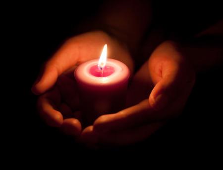 hand houden van een brandende kaars in het donker