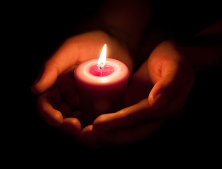 hand holding a burning candle in dark Stockfoto