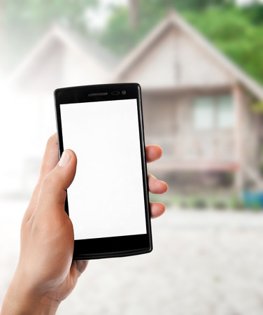 bungalow: Hand holding smart phone on Beach bungalow background.