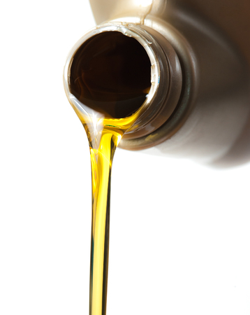 engine: pouring engine oil from its plastic container on white background,Selective focus
