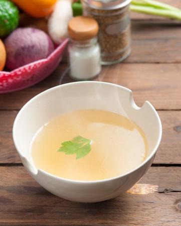 sopa de pollo: tazón de caldo y verduras frescas en madera Foto de archivo