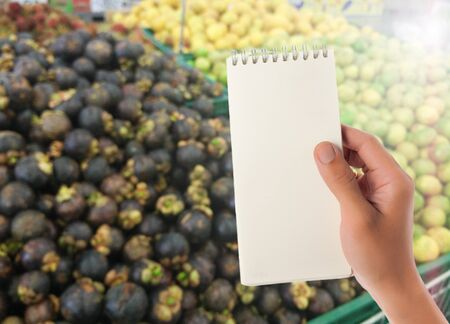 blank space: Hand hold blank notepad with space for text,Blur fruits shelf in supermarket background