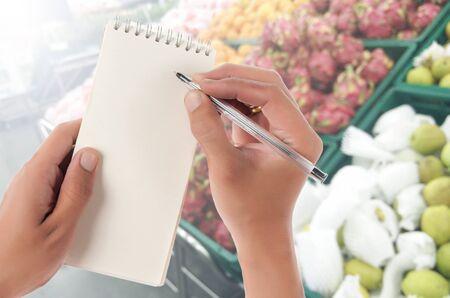 supermercado: Mano mantenga la libreta en blanco con espacio para texto, Blur frutos estante en fondo supermercado