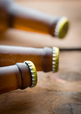 beer bottle: Bottles of beer with drops on brown wooden background
