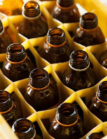 alcohol series: Empty brown bottles in a yellow crate