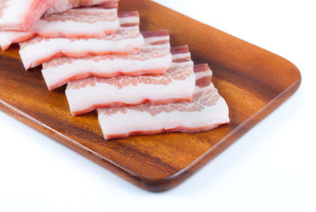 uncooked bacon: Pork belly sliced on wood