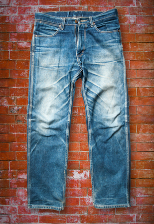 trouser: Blue jeans trouser on orange brick wall Stock Photo