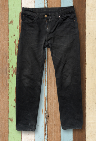 trouser: Black jeans trouser on wood background Stock Photo