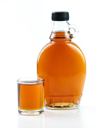 jarabe: jarabe de arce en botella de vidrio en el fondo blanco Foto de archivo