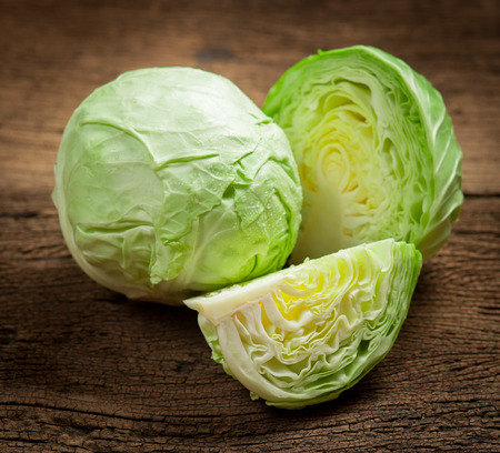 the cabbage: cabbage and cutted cabbage on wooden Stock Photo