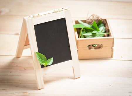 herbs boxes: Empty Blackboard Menu with basilic leaves on a wooden