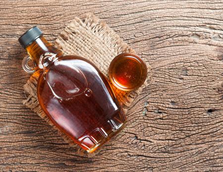 кленовый сироп в стеклянной бутылке на деревянный стол