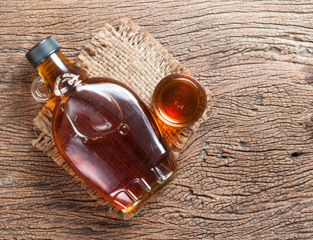 botella: jarabe de arce en botella de vidrio en la mesa de madera