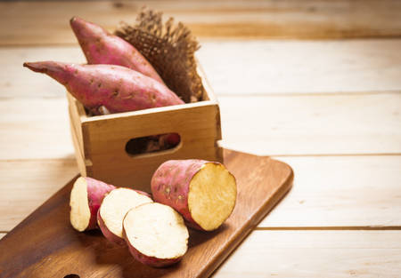 Raw sweet potatoes on a wooden background . Selective focus