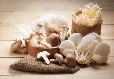 Variety of Mushrooms in a basket on wood