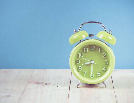 alarmclock: Green alarm clock on wood, vintage color toned image
