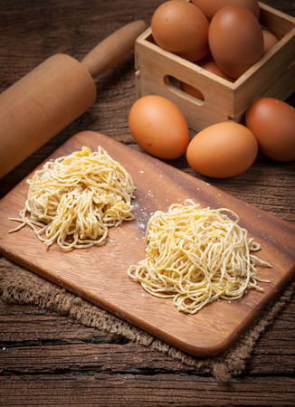 eating noodles: Yellow noodles drying with eggs on wood background