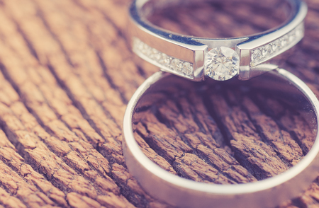 diamond rings: wedding rings on wood,vintage color toned image