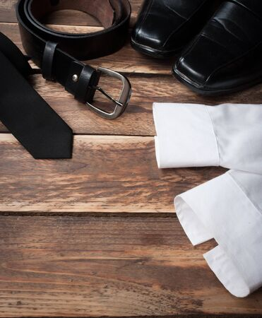 stylish men: Mans style accessories,shirt with a bright tie, shoes and a belt on wooden background